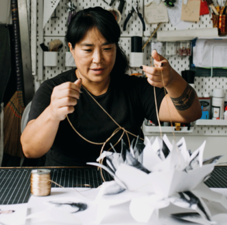 Photographer & Book Artist Colette Fu pulling the strings of a pop-up in her studio.