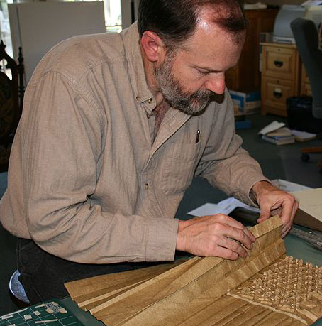 Mathematician and Engineer, Roberrt Lang, engrossed in folding a sheet of origami