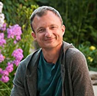 Headshot of Book Artist, Shawn Sheehy smiling at the viewer from a garden