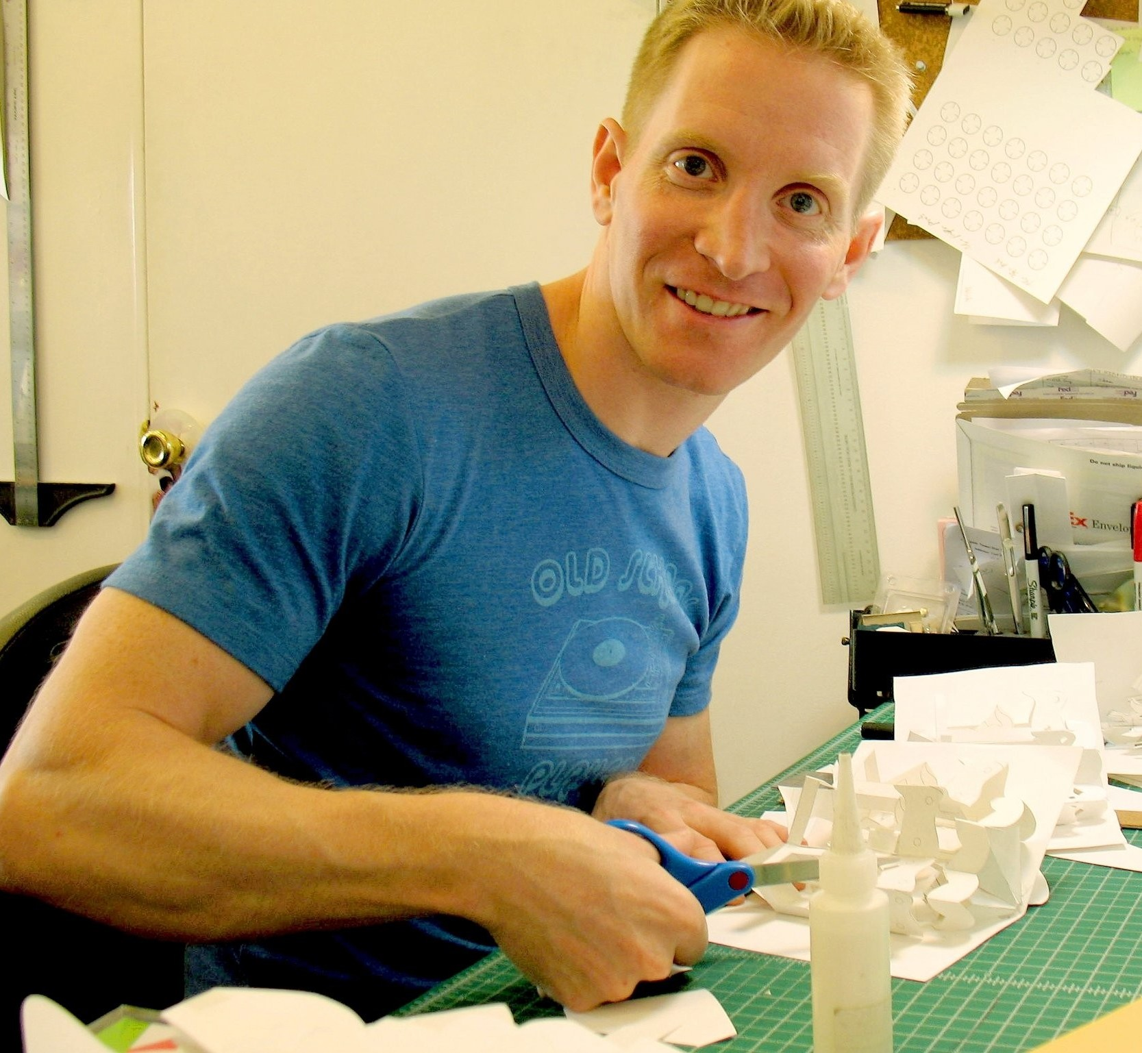 Paper Engineer, Robert Sabuda, sitting at his desk cutting a pop-up mock-up