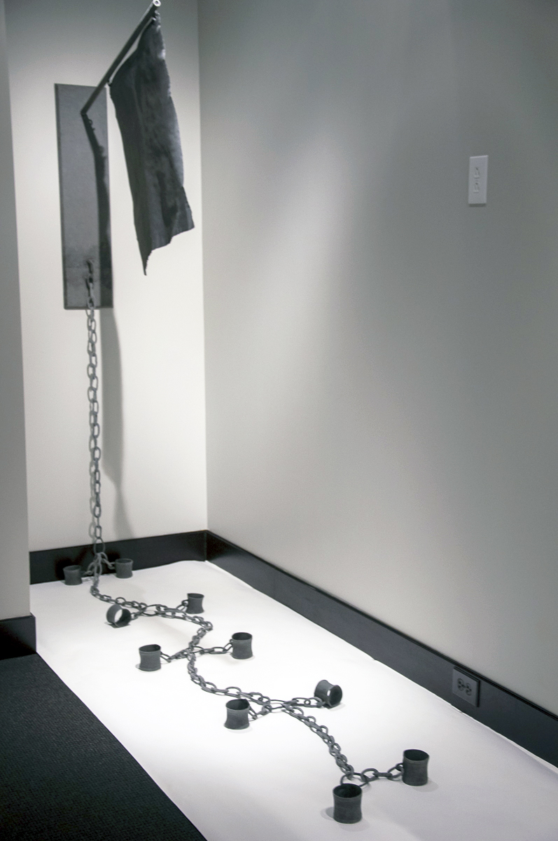 """The National Narrative"" consists of a black flag hanging out away from the wall with a length of chain with five sets of cuff lengths attached at intervals along the chain."