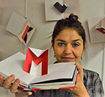 A photo of graphic designer and pop up artist Marion Bataille holding ABC3D open to the M page